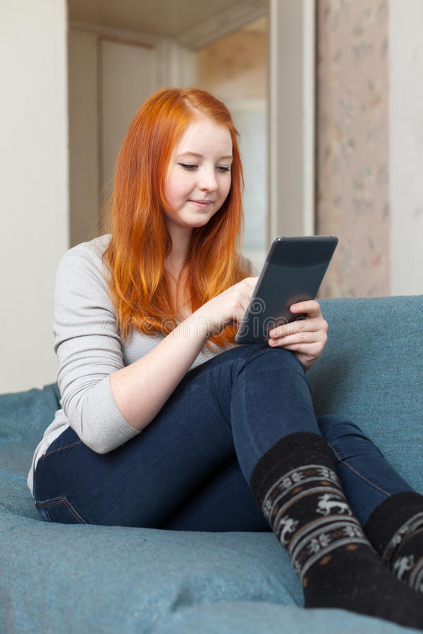 A menina do adolescente lê o e-leitor ou o tablet pc imagem de stock royalty free