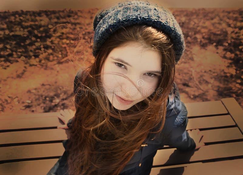 Menina do adolescente no casaco azul e no chapéu feito malha no parque do outono foto de stock
