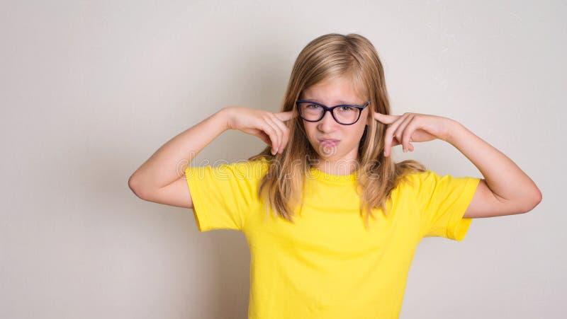 A menina do adolescente nos monóculos fechou suas orelhas para não escutar com c imagens de stock
