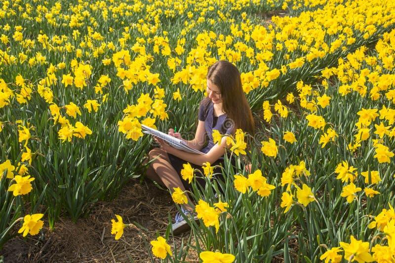 A menina do adolescente pinta as flores, sentando-se no campo de florescência imagens de stock