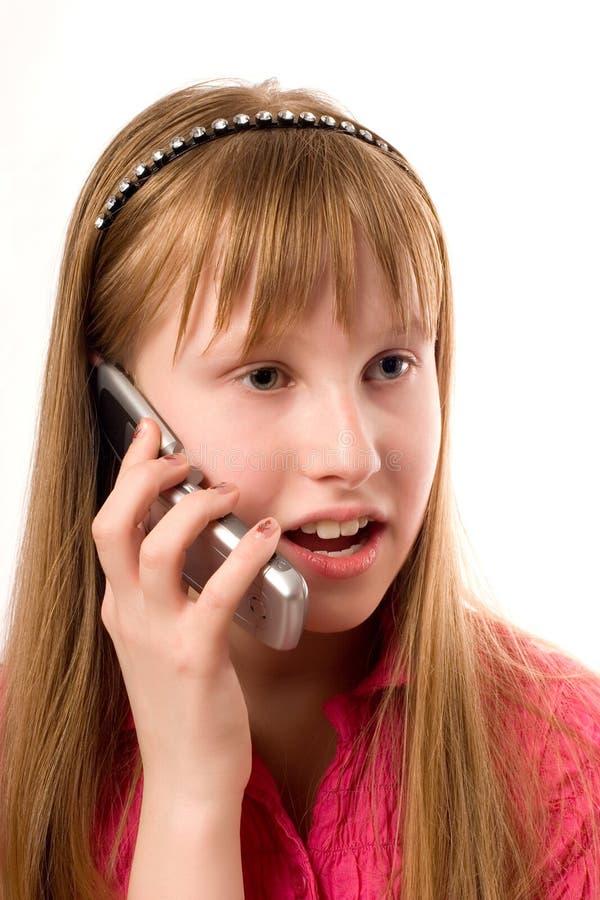 Menina do adolescente que fala pelo telefone móvel isolado sobre fotos de stock royalty free