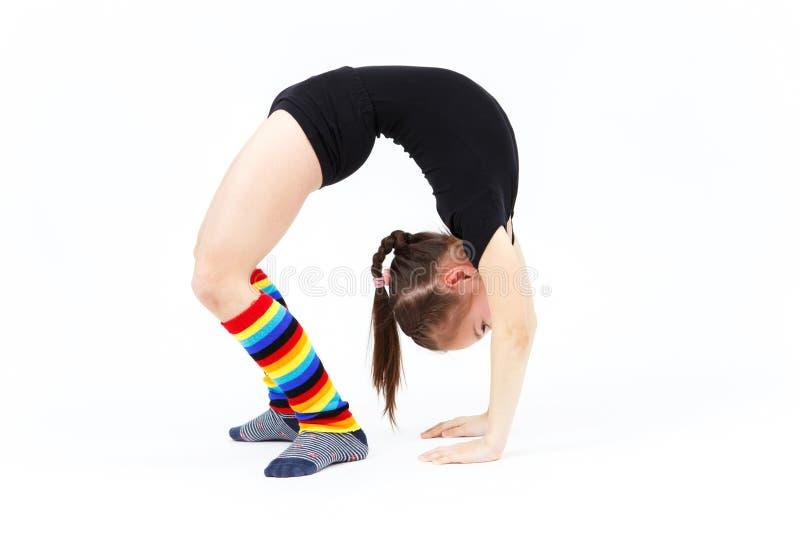 A menina do adolescente que faz a ginástica exercita em um fundo branco foto de stock royalty free