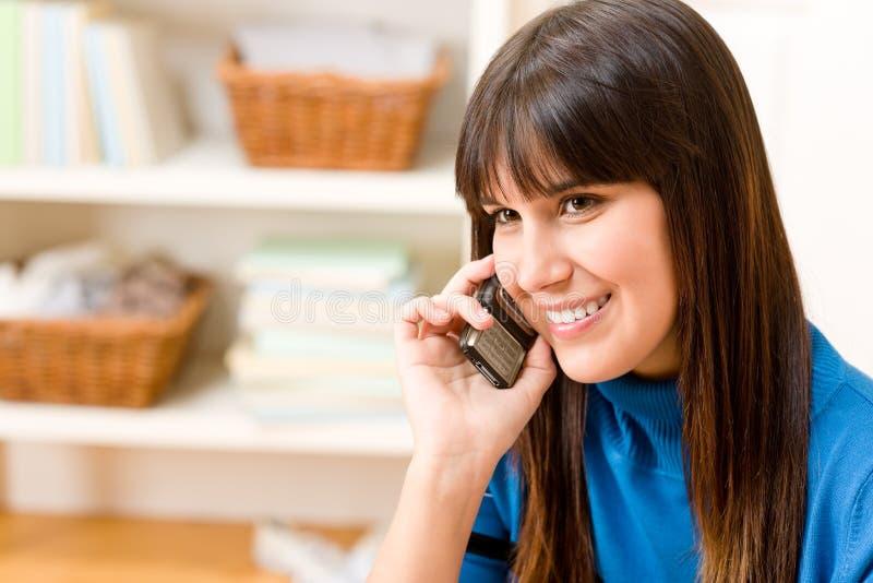A menina do adolescente relaxa para casa - no telefone imagem de stock
