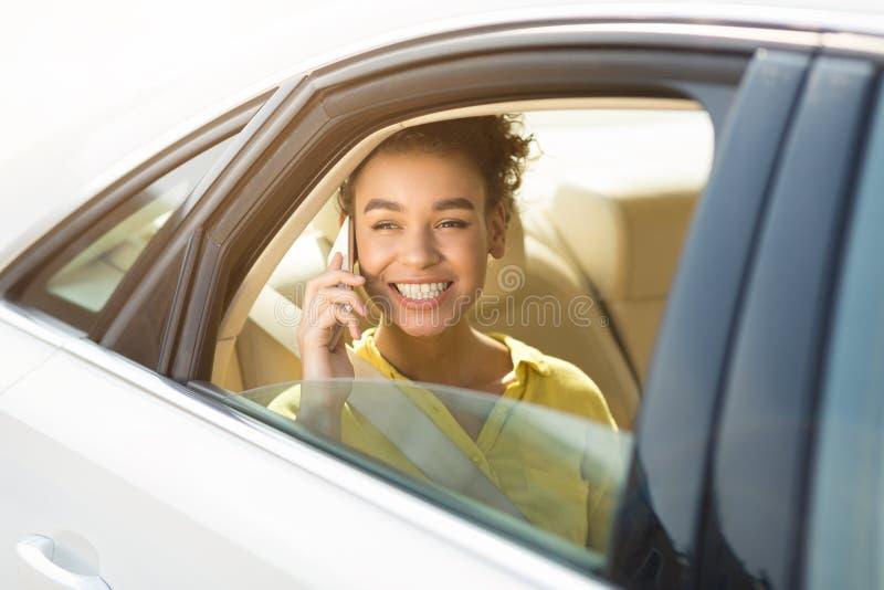 Menina do Afro que fala no telefone, sentando-se no carro imagens de stock