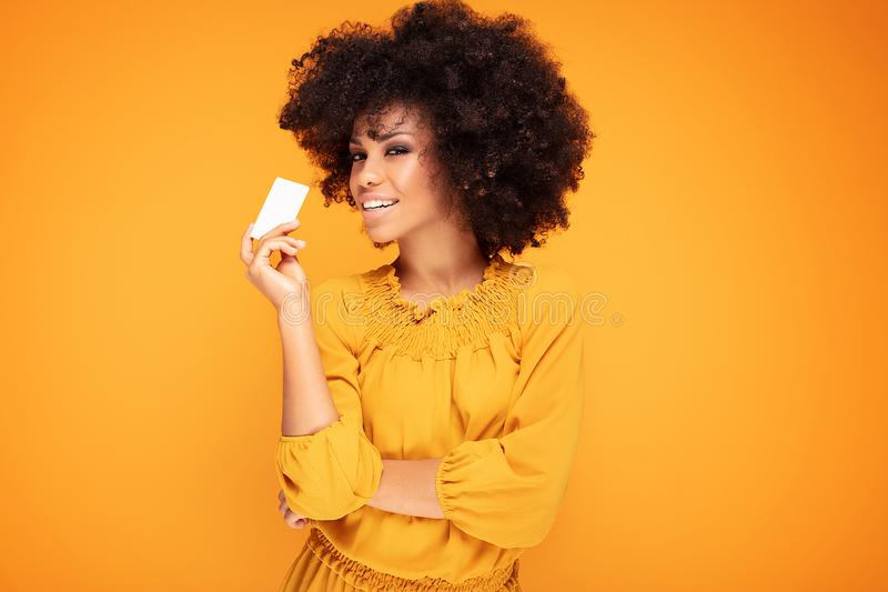 Menina do Afro que guarda o cartão de crédito à disposição imagem de stock