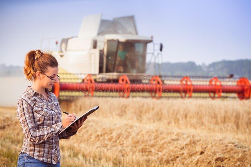 A menina do agrônomo nos vidros mantém uma contabilidade da colheita no dobrador imagens de stock