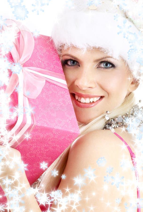 Menina do ajudante de Santa com a caixa e o floco de neve cor-de-rosa de presente foto de stock