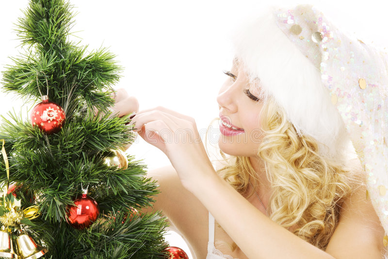 Menina do ajudante de Santa que decora a árvore de Natal fotografia de stock