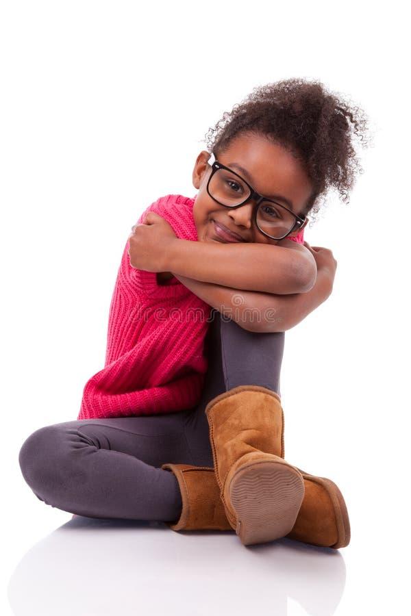 Menina do americano africano assentada no assoalho