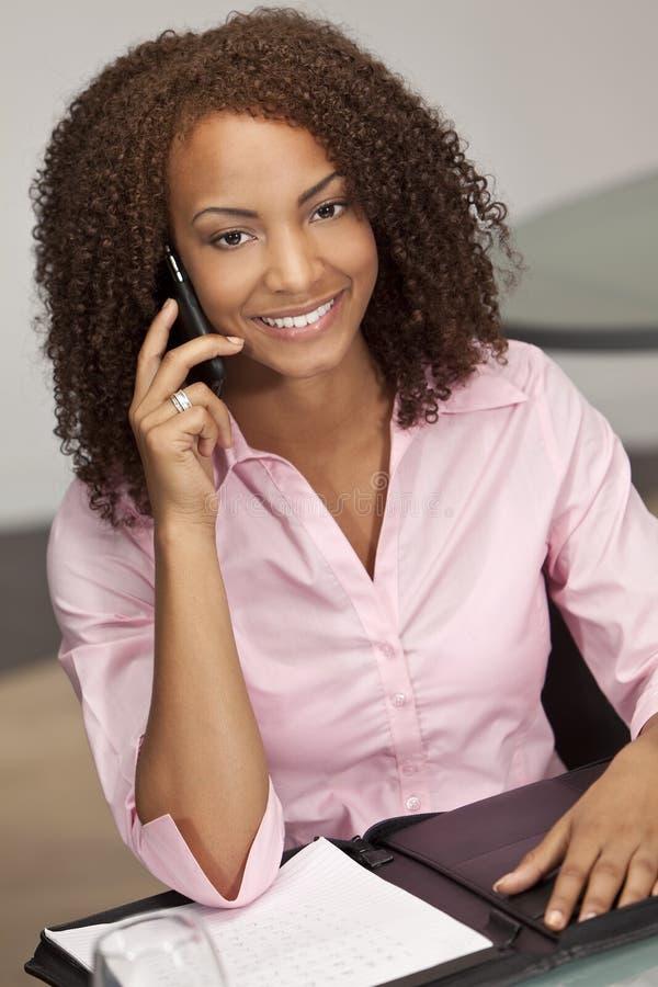 Menina do americano africano de raça misturada no Phon da pilha fotografia de stock royalty free