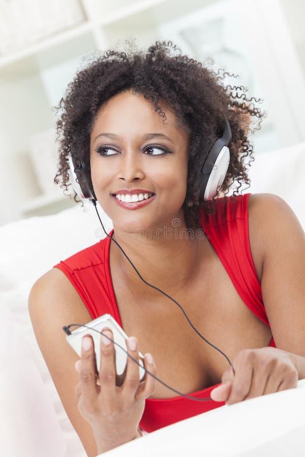 Menina do americano africano que escuta a música em casa fotografia de stock royalty free