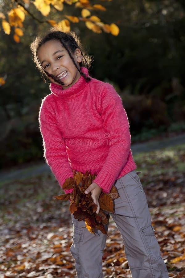 Menina do americano africano que joga com folhas da queda imagem de stock