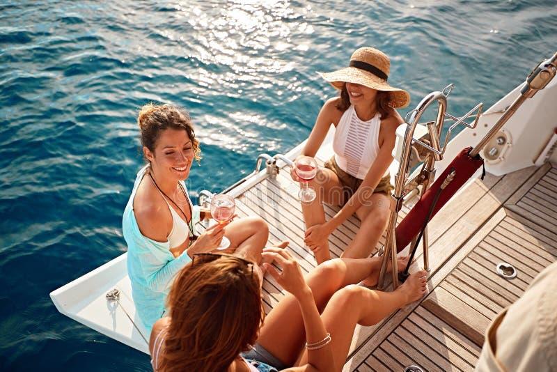 A menina do amigo que tem o partido no barco de navigação e que bebe o vinho no dia de verão fotografia de stock royalty free