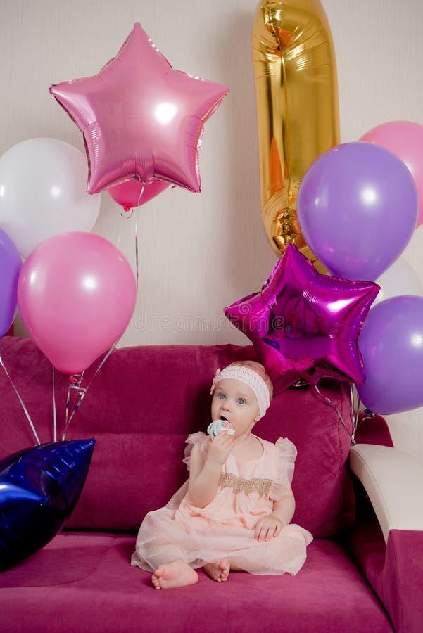 A menina do aniversário morde um pedaço de bolo que senta-se no sofá cercado por balões fotos de stock royalty free