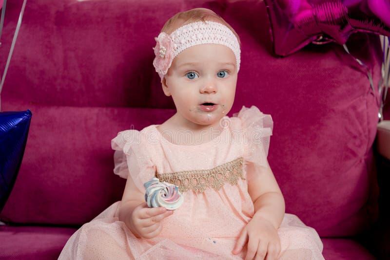 A menina do aniversário morde um pedaço de bolo que senta-se no sofá cercado por balões Retrato do close up imagens de stock