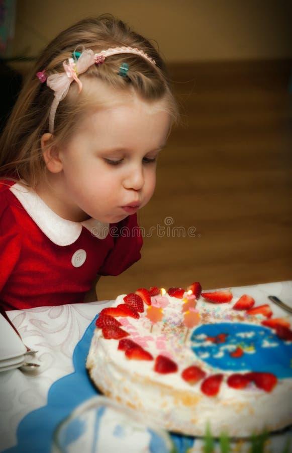 Menina do aniversário que funde para fora velas fotos de stock
