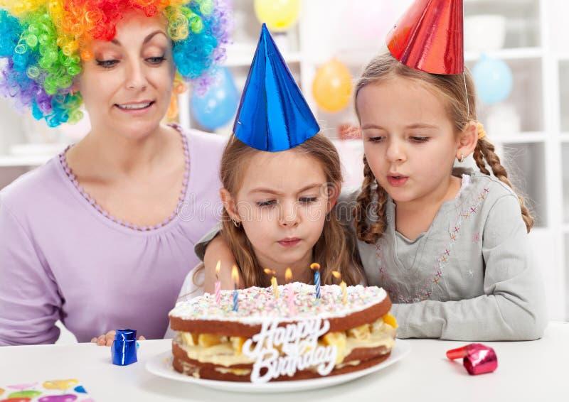 Menina do aniversário que funde para fora velas em um bolo foto de stock