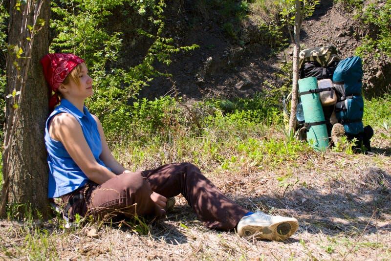 Menina do Backpacker que relaxa sob a árvore fotos de stock royalty free