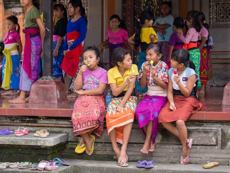 Menina do Balinese que descansa depois que a escola dança e comendo o gelado Ubud, Indonésia foto de stock royalty free