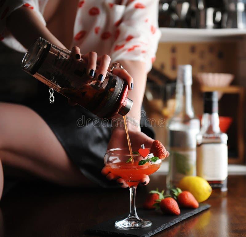 A menina do barman derrama o cocktail do uísque do abanador no vidro decorado com pino e hortelã do coração Morangos na placa fotografia de stock