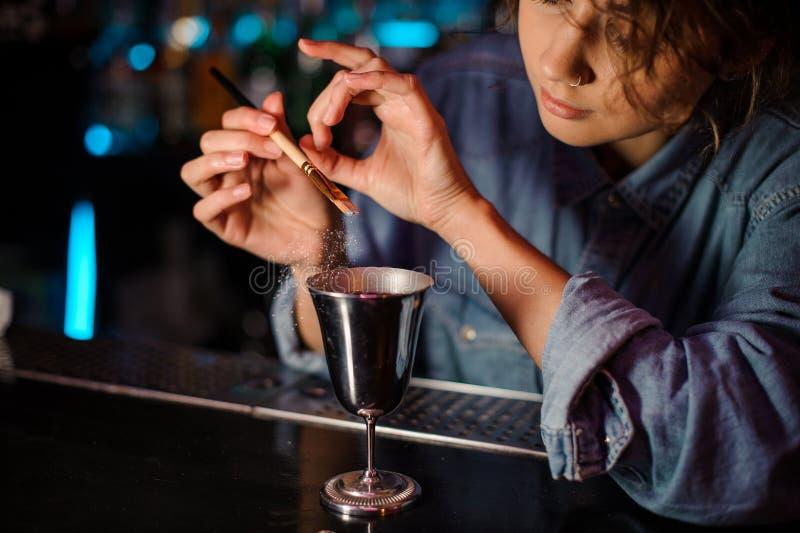 Menina do barman que adiciona um brilho da escova a um vidro de cocktail com bebida alcoólica foto de stock royalty free