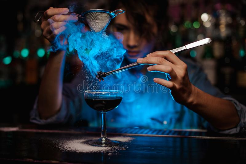 Menina do barman que adiciona a um cocktail marrom e para derramar em um badian ardido na pinça um açúcar pulverizado na luz azul fotografia de stock