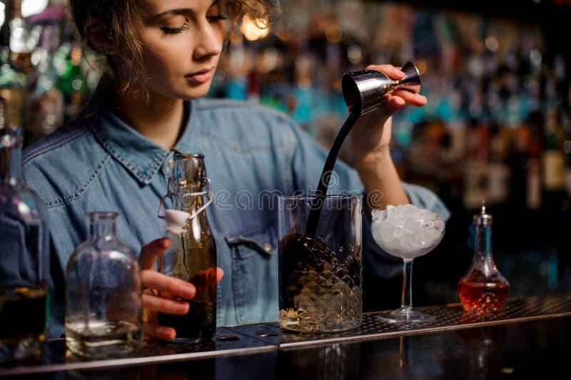 A menina do barman que derrama ao copo de vidro da medição com gelo cuba uma bebida alcoólica marrom do jigger de aço imagem de stock