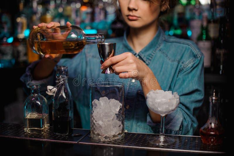 Menina do barman que derrama ao jigger de aço uma bebida alcoólica imagem de stock royalty free