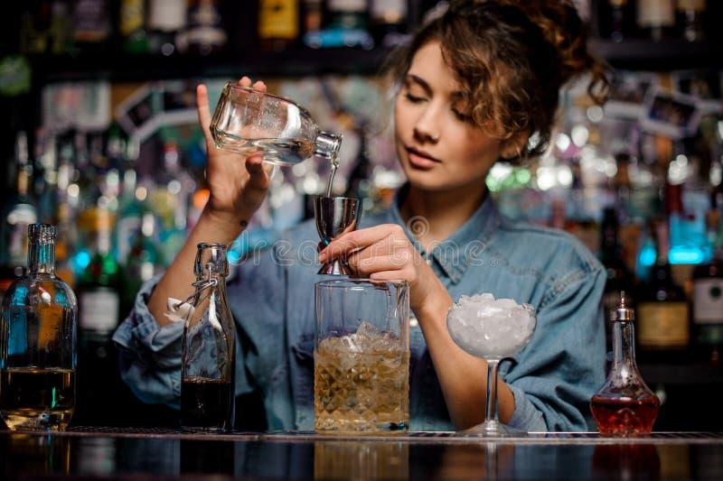 Menina do barman que derrama ao jigger de aço uma bebida alcoólica no contador da barra imagens de stock