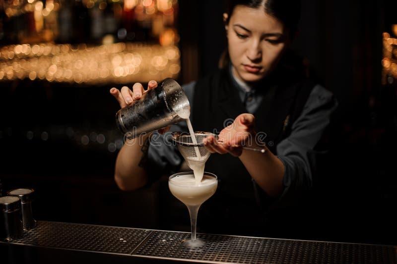 Menina do barman que derrama um cocktail delicioso do abanador de aço através da peneira fotografia de stock