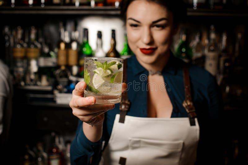 Menina do barman que guarda um cocktail fresco com cal e hortelã fotografia de stock