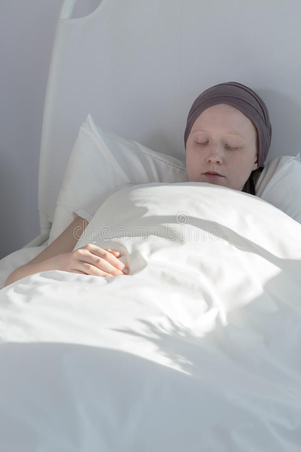 Menina do câncer que fica na cama fotos de stock