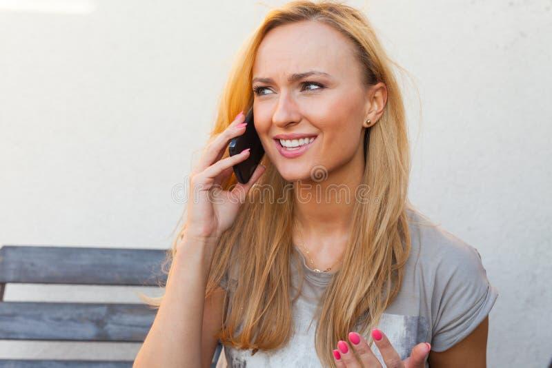 Menina do cabelo louro que senta atrás da tabela uma fala pelo telefone fotografia de stock royalty free
