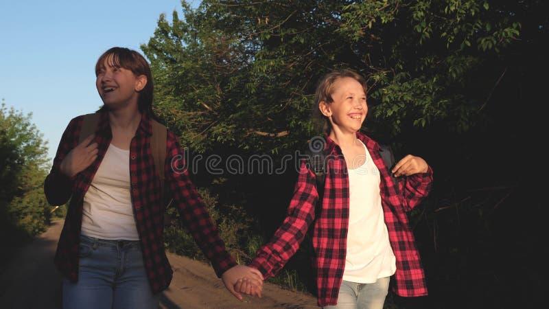 Menina do caminhante As meninas adolescentes viajam e guardam as m?os Viajantes das crian?as as meninas com trouxas est?o na estr foto de stock