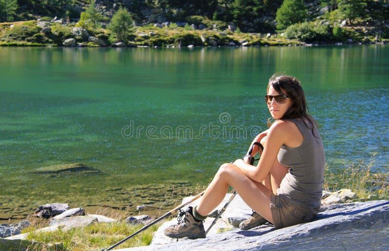 A menina do caminhante levanta em uma pedra com bengalas da montanha fotografia de stock royalty free