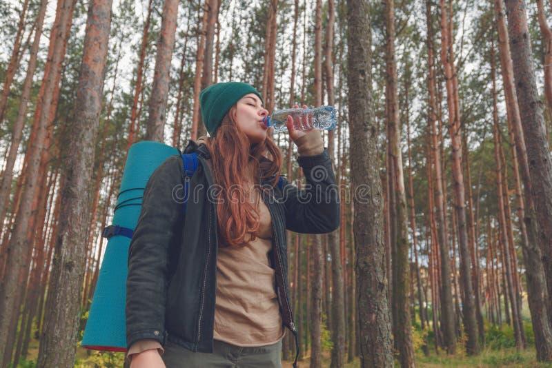 Menina do caminhante que aprecia a água Turista feliz da mulher com água potável da trouxa da garrafa na natureza fotos de stock
