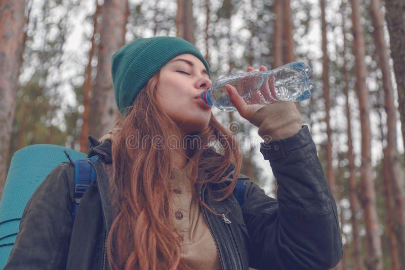 Menina do caminhante que aprecia a água Turista feliz da mulher com água potável da trouxa da garrafa na natureza imagens de stock royalty free