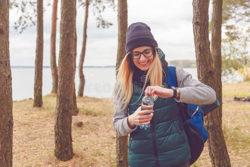 Menina do caminhante que aprecia a água Turista feliz da mulher com água potável da trouxa da garrafa na natureza fotografia de stock royalty free