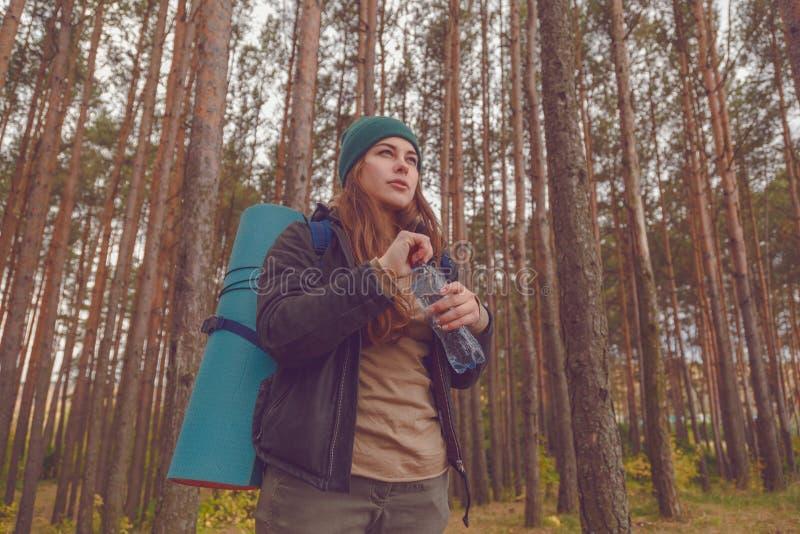 Menina do caminhante que aprecia a água Turista feliz da mulher com água potável da trouxa da garrafa na natureza fotografia de stock