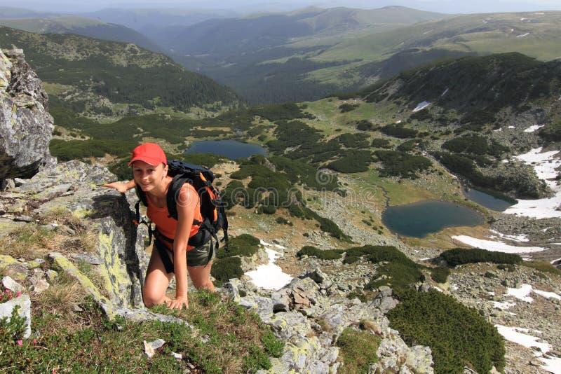 Menina do caminhante que escala sobre a montanha fotografia de stock royalty free