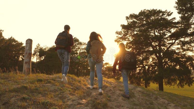 Menina do caminhante três meninas viajam, andam através das madeiras para escalar o monte para exultar e levantar suas mãos para  foto de stock