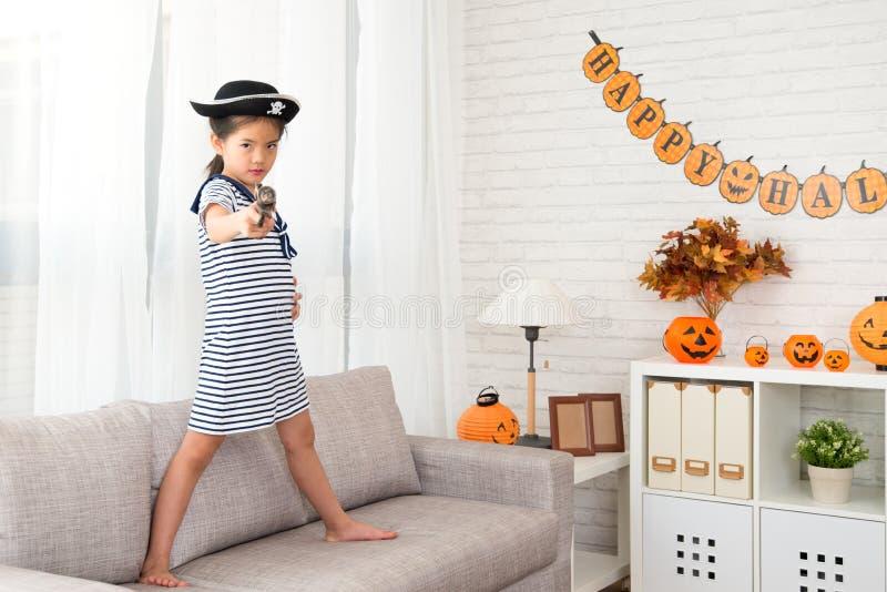 Menina do capitão que guarda uma arma do brinquedo do pirata imagem de stock royalty free