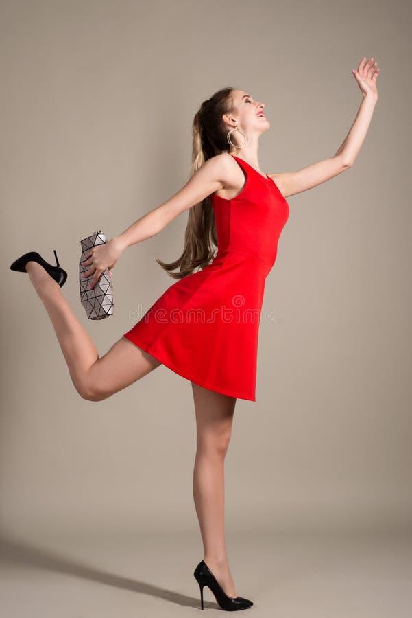 Menina do cliente no vestido vermelho que mantém corridas da bolsa isoladas no fundo cinzento imagens de stock