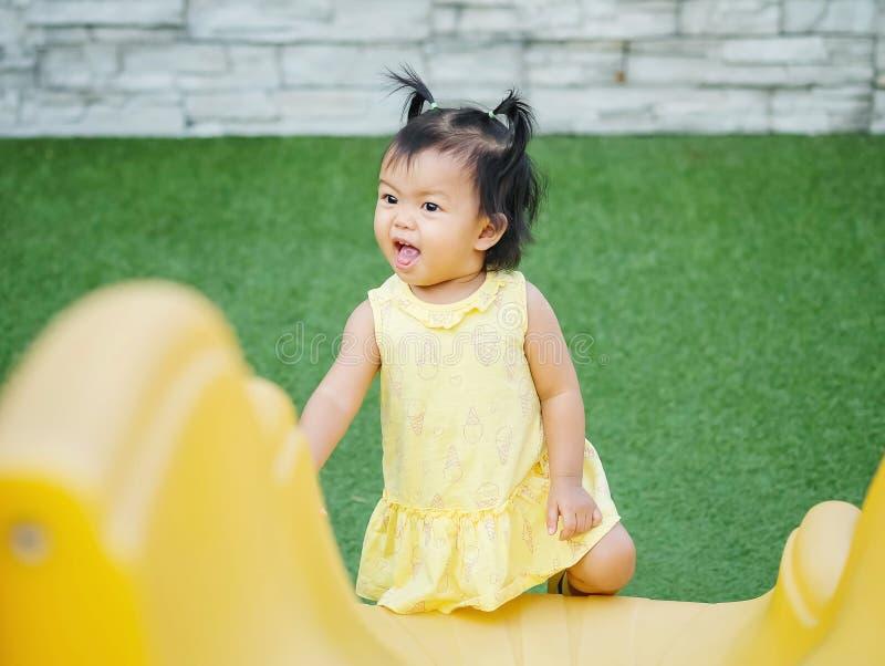 Menina do close up com movimento engraçado quando jogar um slider no fundo do campo de jogos imagens de stock royalty free