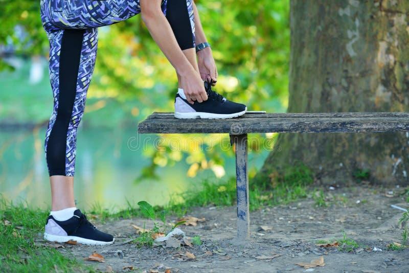 Menina do corredor que amarra sapatas dos laços no banco fotografia de stock