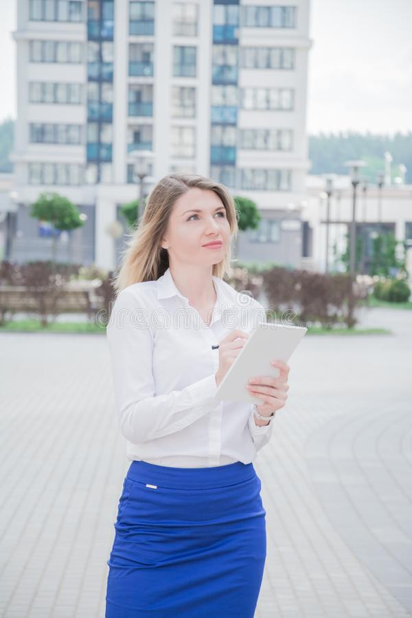 A menina do corretor de imóveis com um caderno em suas mãos inspeciona a área residencial moderna imagem de stock