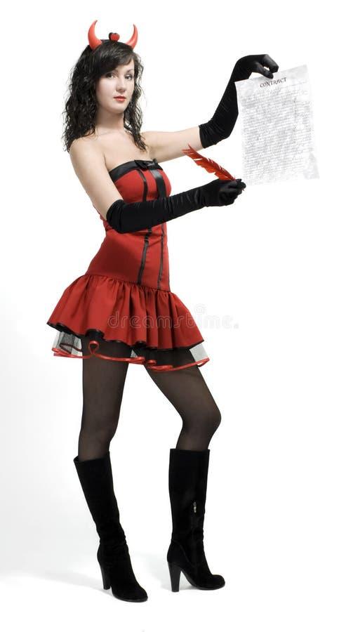 Menina do diabo vermelho da beleza com um contrato e uma pena foto de stock royalty free