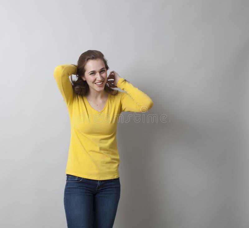 Menina do divertimento 20s que põe seu cabelo na forma para o tiro da foto fotografia de stock