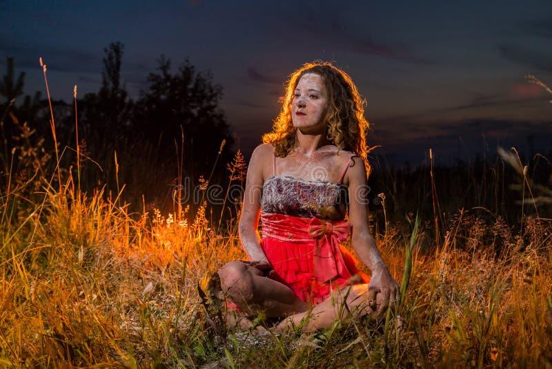 Menina do duende em uma parte superior preta e saia vermelha na grama do campo na noite imagens de stock royalty free