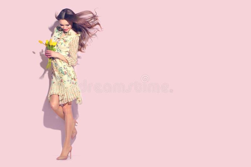 Menina do encanto da beleza com as flores da tulipa da mola Jovem mulher bonita que levanta com o ramalhete das tulipas Vestido c imagem de stock